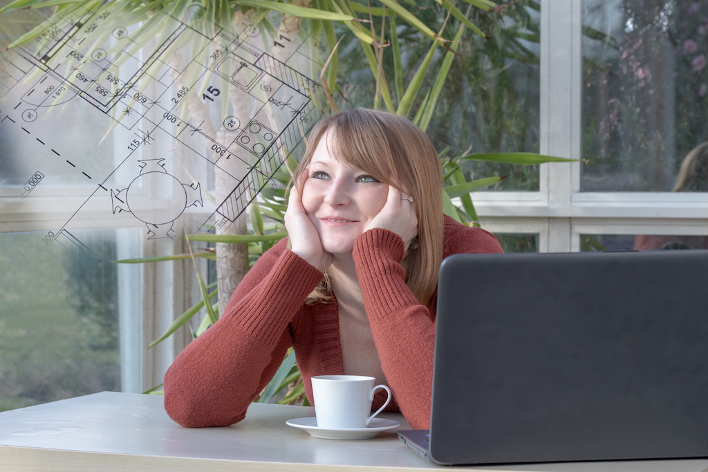 woman daydreams of home layout design, imagining blueprints, while seated in sunroom