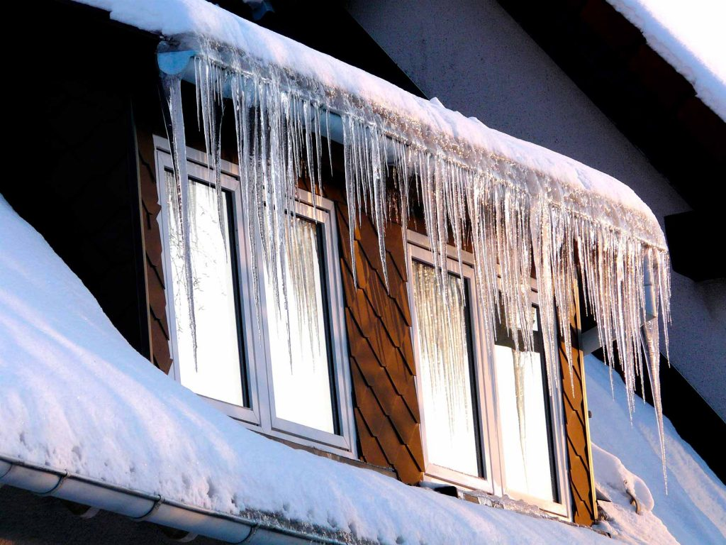 Ice dams forming on gutters can cause winter storm damage