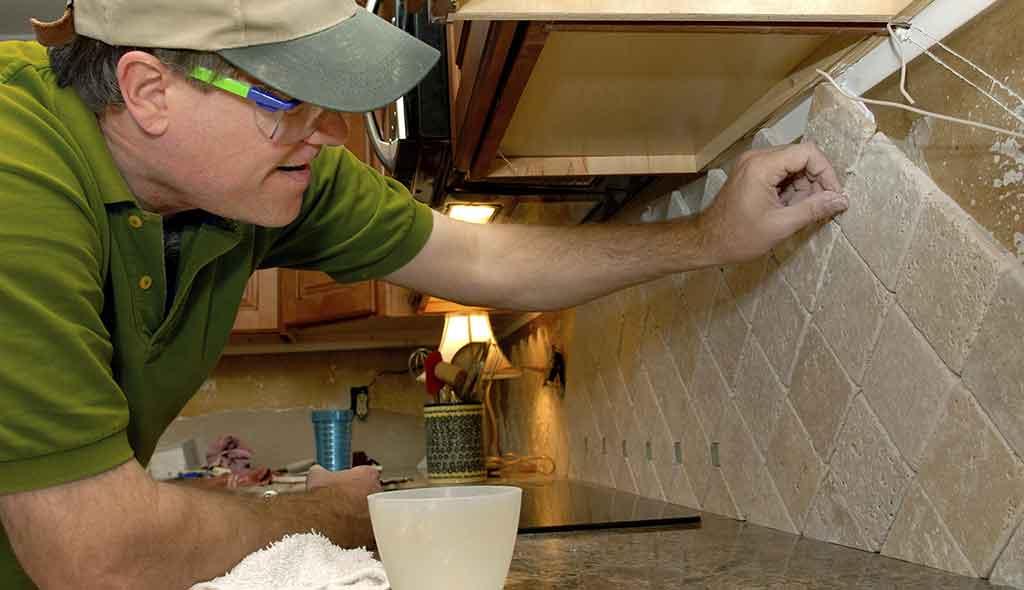 Contractor installing kitchen backsplash tiles