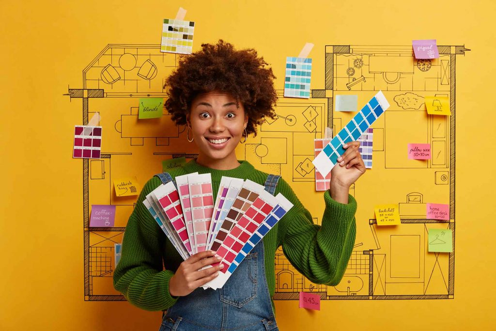 Young woman holding color swatches, making decisions in remodeling