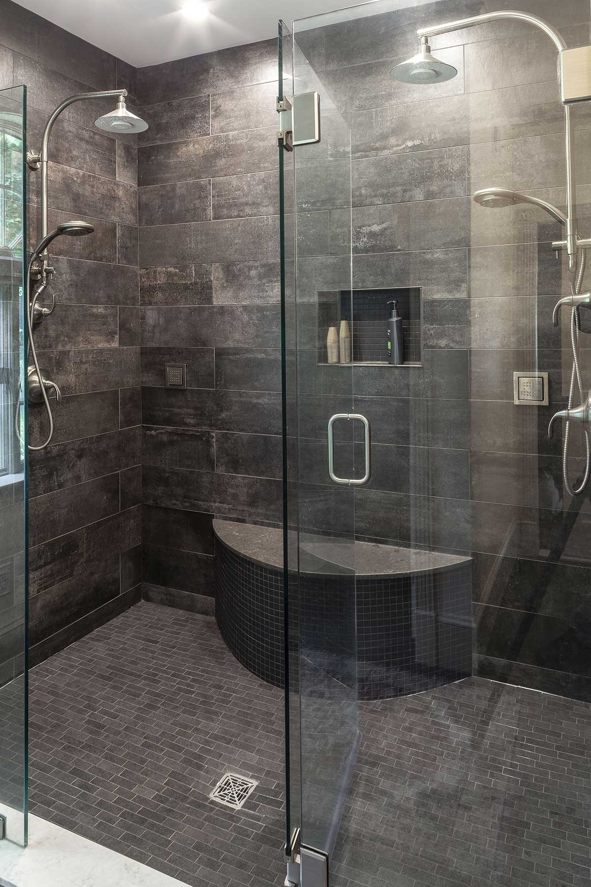 Luxurious multi-head walk-in shower with dark tile walls and floor