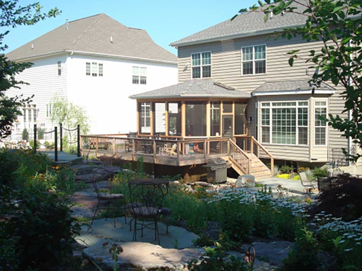 View of screen room, deck, and hardscaping from yard